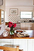 Vase of roses, open book and cake in country-house kitchen