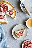 Lemon Tarte serviert mit Sahne, Erdbeeren und Honig (Aufsicht)