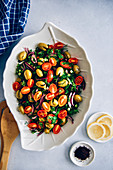 Green olive salad with herbs, onion, flavored with lemon, olive oil and pomegranate molasses