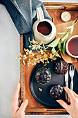 Person holding a wooden tray with healthy chocolate zucchini muffins on a black plate sand tea