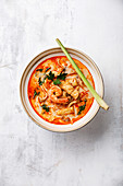 Tom Yam Kung (Spicy Thai seafood soup with shrimp, coconut milk and lemon grass) in bowl
