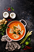 Tom Yam Kung (Spicy Thai seafood soup with shrimp, coconut milk and lemon grass) in casserole dish