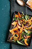 Warm pumpkin salad with baby spinach, onions and rocket