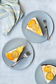 Slices of iced orange cake on plates with forks