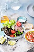 Blattsalat mit Rinderfilet, Cocktailtomaten, Tomatenchutney und Limetten