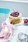 A pancake cake with fresh berries, raspberries, cherries and blueberries