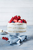 A naked cake with raspberries, strawberries, redcurrants and blueberries