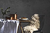 A wire chair with a sheepskin rug with copper pots and winter dishes