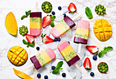 Strawberry, mango, kiwi and blueberry ice cream pops with fruits