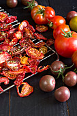 Getrocknete Tomaten auf einem Rost ausgebreitet, daneben frische, bunte Tomaten