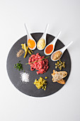 Beef tartare with egg, sauces, herbs and spices