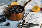 Brombeeren im Kupfertopf, Zucker, Zitronen und Rezeptbuch