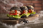 Schwarze Halloween-Burger mit Spinnweben
