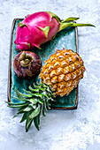 Dragon fruit, mangosteen and pineapple on a blue craft plate