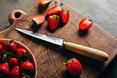 Frische Erdbeeren in Schälchen und halbiert mit Messer auf Holzbrett