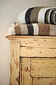 Gefaltete Web-Decken auf einem Schrank mit abgenutzter Farbe