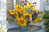 Erntedankstrauß mit Sonnenblumen, Oregano und Ähren am Fenster