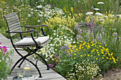 Stuhl auf Holzterrasse in einer Blumenwiese