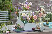 Sträuße mit Rosen, Glockenblumen und Oregano in Flaschenträger