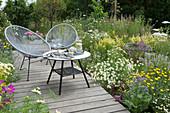 Kleine Sitzgruppe auf Holzterrasse in einer Blumenwiese