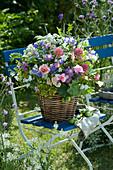 Üppiger Sommerstrauß aus Rosen, Stauden und Wiesenblumen im Korb