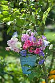Kleiner Strauß aus Rosen und Stauden am Zierapfelbaum aufgehängt