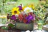 Gesteck aus Sonnenblumen, Dahlien und Schafgarbe in Jardiniere