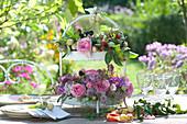 Romantische Tischdekoration mit Rosen, Sterndolde, Dahlien und Früchten in Etage