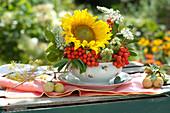 Kleines Gesteck aus Sonnenblume, Wiesenkümmel und Vogelbeeren