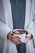Frau hält einen Becher Tee oder Glühwein mit Sternanis und Orangenscheibe