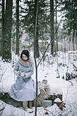 Woman drinking tea in snowy woods