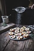 Linzer Weihnachtsplätzchen mit Puderzucker bestreuen