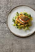 Fried seabream fillet on a potato salad with an orange salsa verde