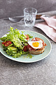 Ham and egg on toast with a colourful salad and truffle butter