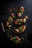 Sourdough bread slices topped with roasted figs with blue cheese, walnuts, ham, rocket and olive oil