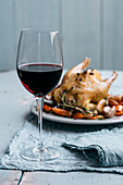 A glass of red wine with roast chicken