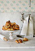 Swedish cinnamon buns on a cake stand and a marble work surface