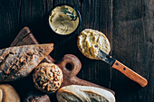 Different types of bread and butter on wooden background