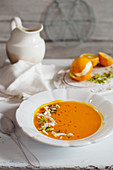 Orange and carrot soup with coconut chips and pistachio nuts
