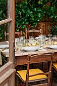 Gedeckter Tisch mit Beerendekoration und frischen Äpfeln