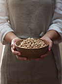 A woman holding a bowl of dried chickpeas
