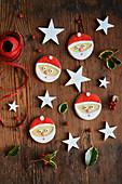 Plätzchen mit Weihnachtsmannmotiv auf Holztisch zwischen Weihnachtsdeko