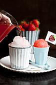 Selbstgemachte Snowcones mit Erdbeersirup übergiessen