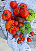 Verschiedene Tomaten auf Holztisch im Garten
