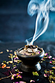 A smoking incense blend in an incense bowl