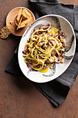 Spaghetti alla carbonara with octopus and bacon served with provolone crisps