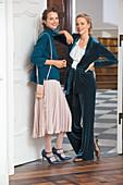 Zwei Frauen in herbstlichen Outfits in Petrol: Pullover mit Plisseerock und Longblazer aus Samt mit Volantbluse und Samthose