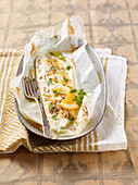 Sea bass fillets with oranges, honey and mustard in paper