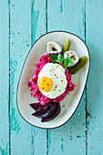 Labskaus (traditional dish from Northern Germany featuring salted meat, potatoes and onions) with rollmops herring and a fried egg