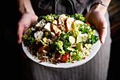 Frau serviert Grünkohl-Avocado-Salat mit Hähnchen
